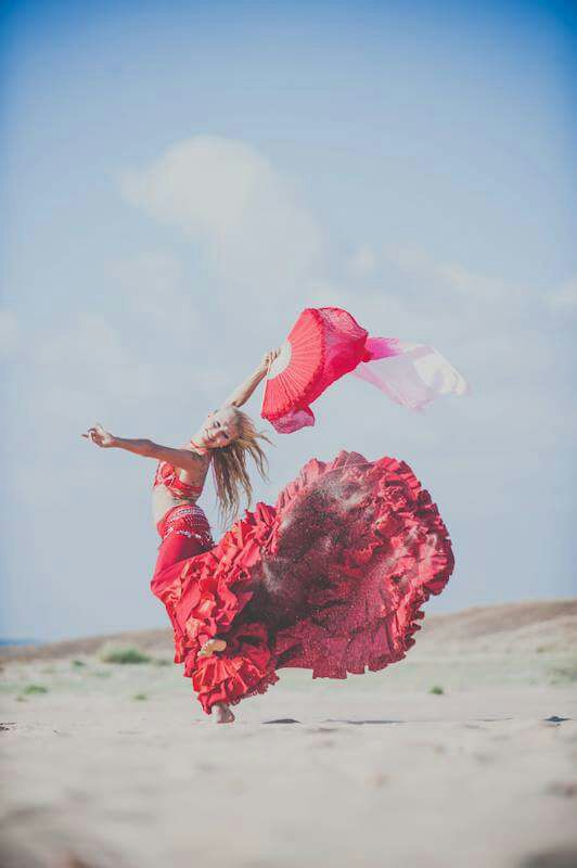 Woman dancing flamenco in a red dress on the beach