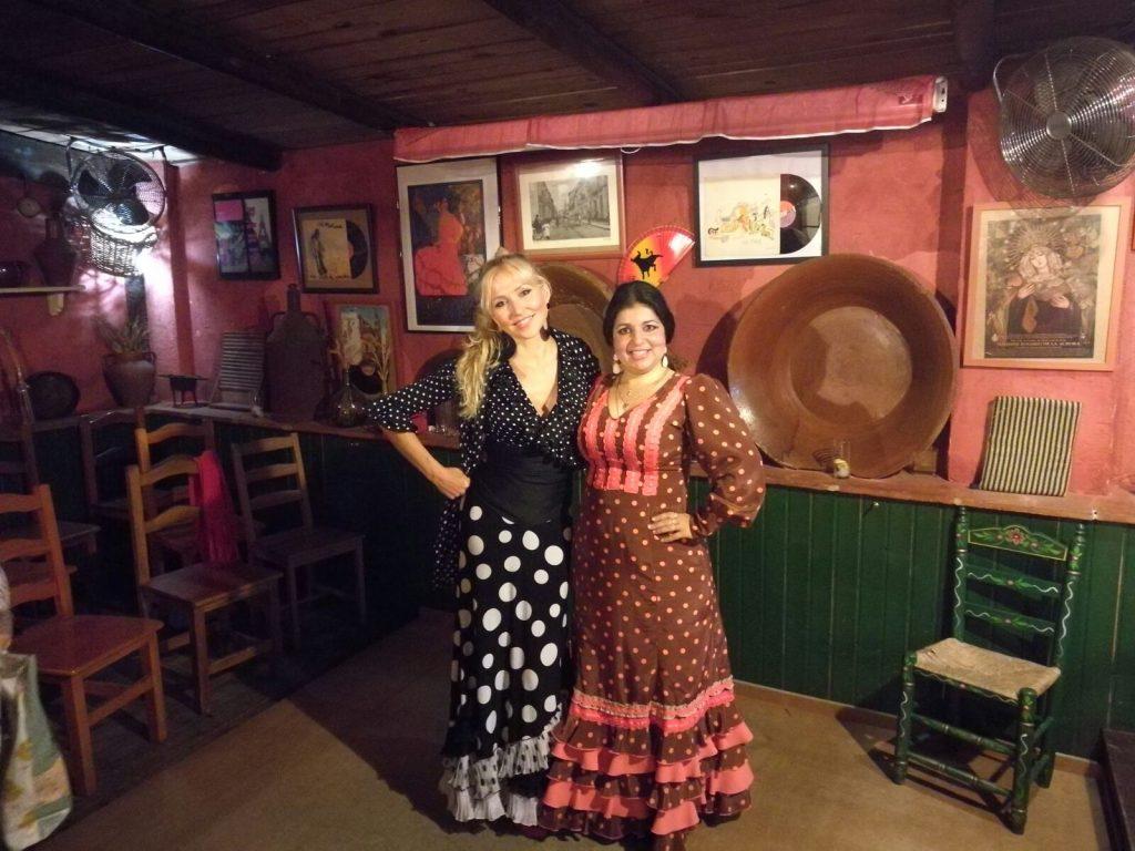 2 women wearing flamenco dresses in a traditional tablao in Seville, Spain