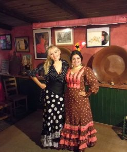 2 women wearing flamenco dresses in a traditional tablao in Seville, Spain
